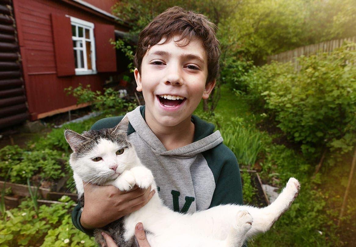 boy carrying a cat